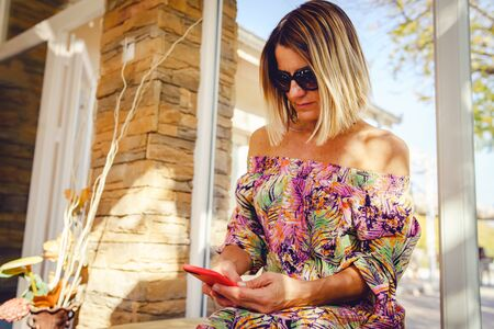 Portrait of mature woman using her mobile smart phone at the cafe or restaurant wearing summer dress in sunny day sitting by the window looking to display photo call or message Reklamní fotografie