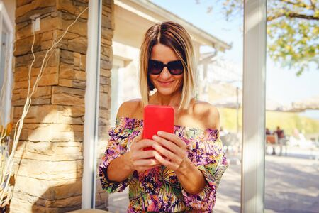 Portrait of mature woman using her mobile smart phone at the cafe or restaurant wearing summer dress in sunny day sitting by the window looking to display photo taking pictures Reklamní fotografie