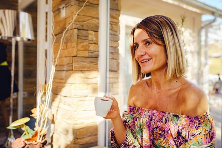 Portrait of woman in cafe or restaurant sitting and holding a cup of coffee while talking wearing summer dress