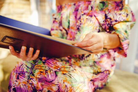 Close up on woman female holding menu at the restaurant midsection in summer dress picking meal