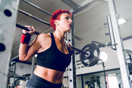 low angle on caucasian woman red short hair training at the gym lifting weight leg workout squats holding barbell powerlifting fitness Reklamní fotografie