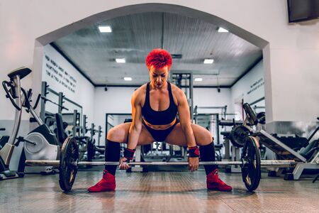 Young caucasian woman working out at gym training deadlift dead lifting weights holding barbel with weight plates strength power female