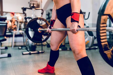 Young caucasian woman working out at gym training deadlift dead lifting weights holding barbel with weight plates strength power female midsection