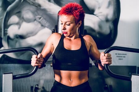 Young caucasian woman red hair athlete training at the gym working on chest pectoral muscles press on the machine fitness body building