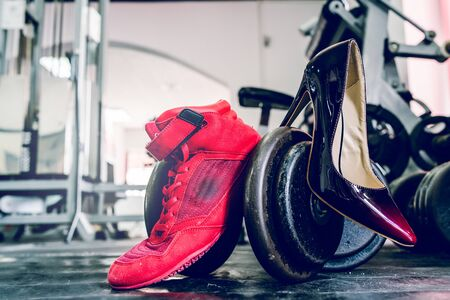 Female weight lifting powerlifting power shoes and spike heels by the dumbbell weight at the gym womans power training identity concept