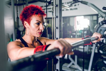 Young caucasian woman with red short hair standing by the barbell at the gym training fitness workout holding the weight bodybuilding power lifting