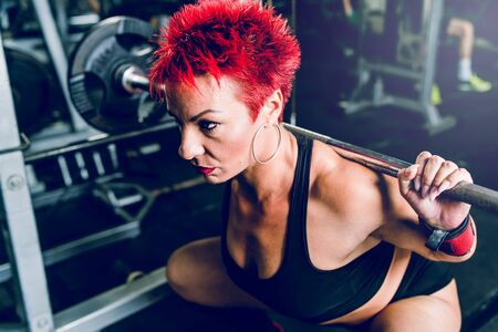 Close up on caucasian woman red short hair training at the gym lifting weight leg workout squats holding barbell powerlifting fitness