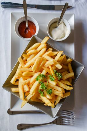 High angle view on the plate on the table with french fries fried potato chips and ketchup and mayonnaise food served with some parsley decorated