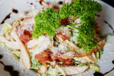 High angle top view on Caesar salad served in a white plate fresh with some parsley