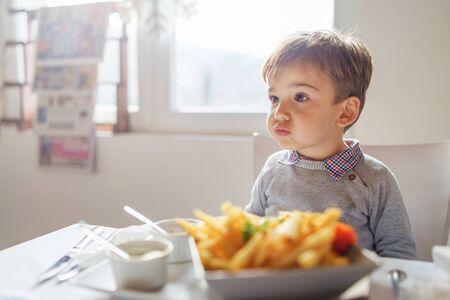 Porträt eines kleinen, süßen, kaukasischen Jungen, der Pommes Frites am Tisch im Restaurant oder zu Hause drei oder vier Jahre alt isst Standard-Bild