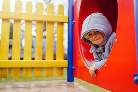 Small caucasian boy in the park on the playground in the red tunnel tube wearing winter coat in autumn day having fun playing smiling