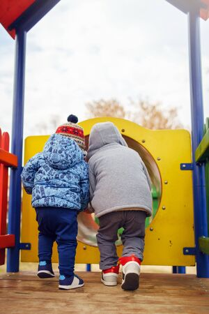 Small two caucasian boys back view in the park on the playground in the red tunnel tube wearing winter coat in autumn day having fun playing walking friendship