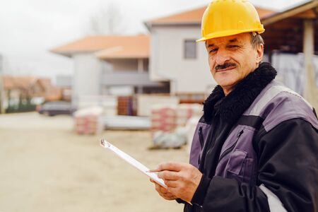 Portrait of caucasian senior man construction worker general laborer building contractor wearing yellow protective helmet holding pen and document checking data report project on the site