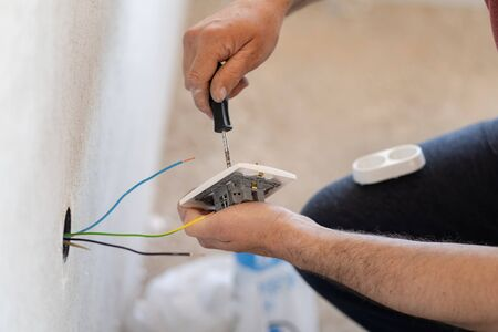 Close up on hands of caucasian man electrician holding screwdriver working on the plug electric on residential electric system installing white AC power socket on gray wall at home repair close up