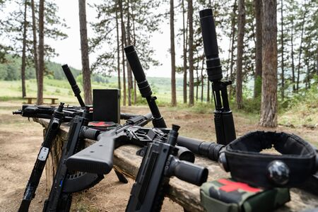Laserwar or lasertag laser war tag equipment weapon on the wooden bench in the woods in sunny day guns rifles gun replica medic kit bomb and head band target sensor close up 版權商用圖片