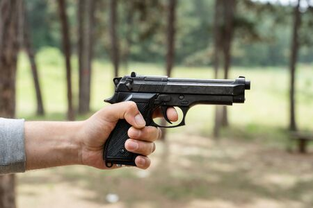 Side view close up on hand with gun caucasian unknown man aiming pointing weapon in forest woods in sunny day ready to shoot aiming to attack or defend