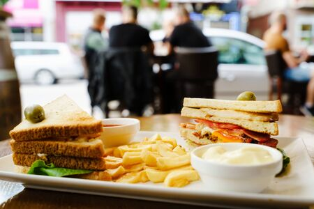 Club sandwich in a plate in restaurant on the table with fresh french fries chips and ketchup and mayonnaise ready for breakfast or lunch front view
