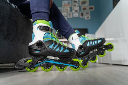 Close up on feet of unknown woman sitting on the sofa bed at home with roller blades inline skates on foot fun freedom motion and youth concept Imagens