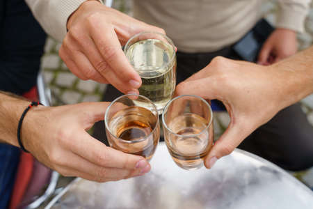 Close up on hands of unknown people holding glasses toasting - Caucasian men celebrating with wine and soda alcohol drink spricer popular in balkan countries - close up top view in day outdoor
