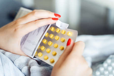 Close up on hands of unknown caucasian woman holding medicine drugs cure - Female taking supplement vitamins mineral while being sick at home - healthcare medicine covid-19 pandemic concept Stock Photo