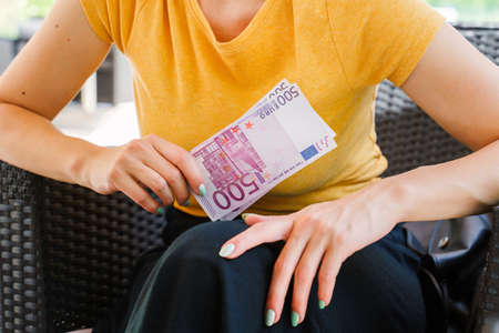 Close up on midsection of unknown caucasian woman holding 500 euro banknotes money while sitting in day - Paying earnings salary wealth concept Stock Photo