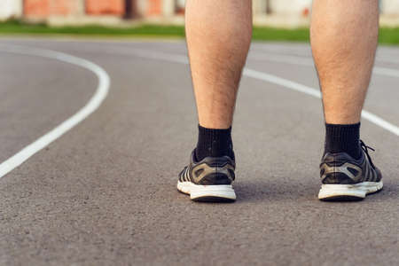 close up on feet of unknown man back view standing on the running track in day outdoor - health and fitness copy space Stock Photo