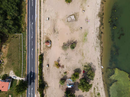 Top down aerial view on the sand beach by Danube river at Brza Palanka town destination with main road beside in summer day - freedom nature travel concept with copy space