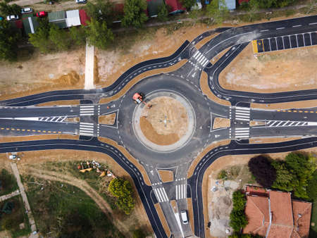 Top down aerial drone view on traffic roundabout road under construction in summer day - Brza Palanka Town in Serbia main road from air - connecting freedom travel and destination concept crossroad