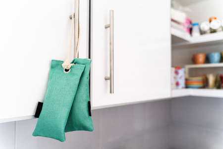 Close up on air purify bag charcoal activated carbon moisture absorber and odor eliminator hanging on kitchen to maintain freshness