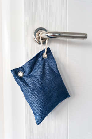 Close up on air purify bag charcoal activated carbon moisture absorber and odor eliminator hanging on the door in apartment at home to maintain freshness and clear smell Stock Photo