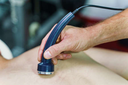 Close up on hand of unknown caucasian therapist holding ultrasonic ultrasound head transducer on skin of patient in treatment using medical equipment to reduce pain - healthcare and medicine concept Stock Photo