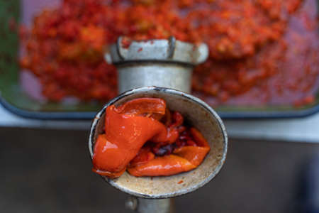 Close up top view outdoor on grinder mill with vegetables preparing paprika baked red pepper for ajvar national dish in balkan - healthy organic food concept Stock Photo - 155418712