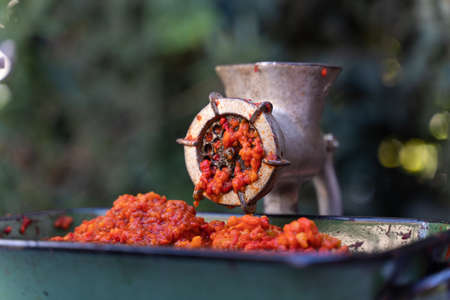 Close up outdoor on grinder mill with vegetables preparing paprika baked red pepper for ajvar national dish in balkan - healthy organic food concept