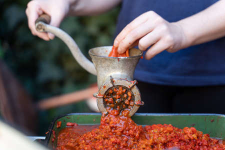 Close up outdoor on female hand on grinder mill for vegetables preparing paprika baked red pepper for ajvar national dish in balkan - healthy organic food concept Stock Photo