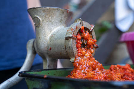 Close up outdoor on grinder mill with vegetables preparing paprika baked red pepper for ajvar national dish in balkan - healthy organic food concept Stock Photo - 155216685