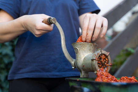Close up outdoor on female hand on grinder mill for vegetables preparing paprika baked red pepper for ajvar national dish in balkan - healthy organic food concept Stock Photo - 155216686