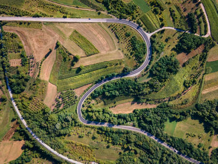 Aerial view top down from above on the country road in mountain range agriculture fields between green grass and trees around - nature travel concept drone photo Europe Serbia in autumn or summer day Stock Photo