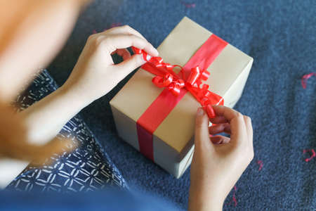 Close up of unknown caucasian woman midsection and hands sitting on sofa at home with preparing wrapped box with red tie ribbon - birthday or holiday present giving and receiving concept Stock Photo - 154926717