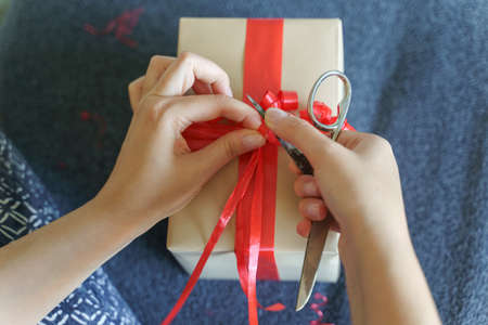 Close up of unknown caucasian woman midsection and hands sitting on sofa at home with preparing wrapped box with red tie ribbon - birthday or holiday present giving and receiving concept