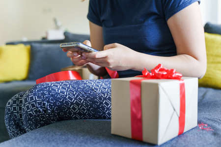 Close up on midsection of unknown caucasian woman sitting on sofa bed at home by birthday present holding mobile smart phone reading congratulation messages - giving and receiving gift concept