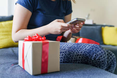 Close up on midsection of unknown caucasian woman sitting on sofa bed at home by birthday present holding mobile smart phone reading congratulation messages - giving and receiving gift concept Stock Photo - 155217121
