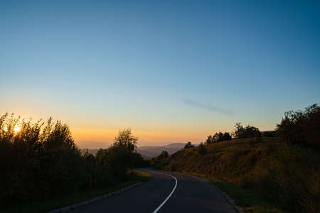 Mountain landscape in sunrise or sunset dark hills with golden sun and blue sky - Road in nature with trees on stara planina Old Mountain in Serbia - tourist destination and freedom concept