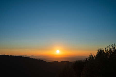 Mountain landscape in sunrise or sunset dark hills with golden sun and blue sky - freedom nature tourist destination concept - stara planina Old Mountain in Serbia Stock Photo