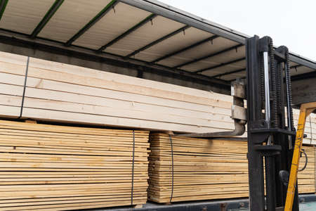 Close up on fork lifter loading or unloading timber wood and planks construction material from the truck in day - copy space building industry concept Stock Photo - 155600959