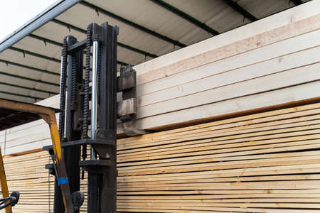 Close up on fork lifter loading or unloading timber wood and planks construction material from the truck in day - copy space building industry concept