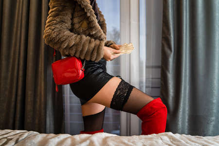Midsection on whore at hotel room - female prostitute escort holding money wearing provocative underwear - prostitution concept
