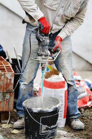 Close up on midsection of unknown man using hand electric drill mixer to prepare adhesive cement glue at construction site Reklamní fotografie