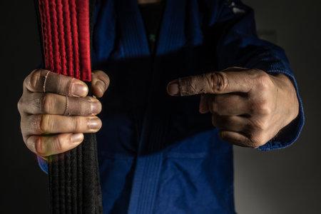Close up on hand of unknown caucasian man holding brazilian jiu jitsu bjj black belt while wearing kimono gi in dark gym - martial arts mastery skill and confidence achievement concept