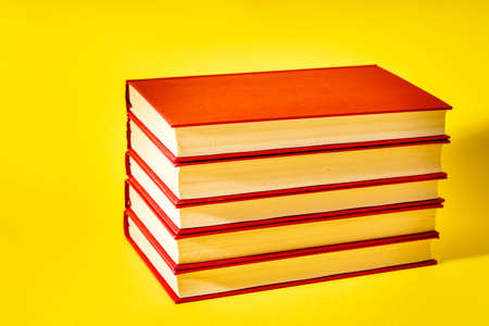 Pile of red books isolated on yellow background close up