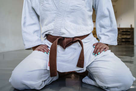 Close up on midsection of unknown woman in white brazilian jiu jitsu or judo kimono gi sitting on tatami mats wearing brown belt on training